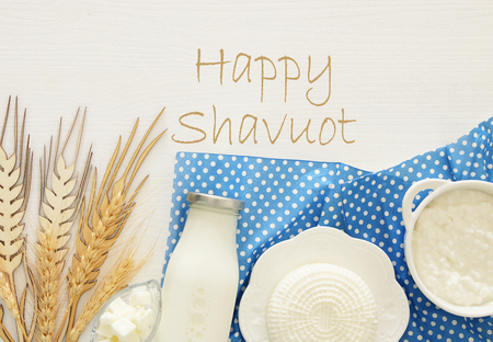 Top view image of dairy products over mint wooden background. Symbols of jewish holiday - Shavuot