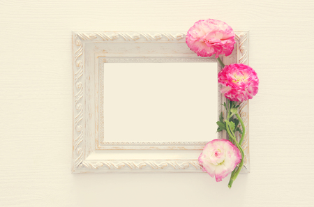 Image of delicate pastel pink beautiful flowers arrangement and empty vintage photo frame over white wooden background. Flat lay, top view. For photography mockup montage Stock Photo