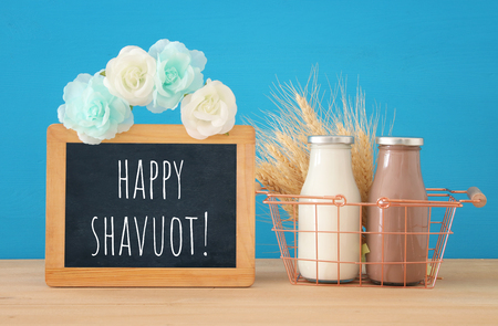 image of milk and chocolate over wooden table. Symbols of jewish holiday - Shavuot
