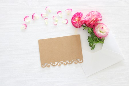 Image of envelope with delicate pastel pink beautiful flowers arrangement over white wooden background. Flat lay, top view