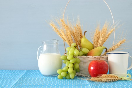 image of milk and fruits over wooden table. Symbols of jewish holiday - Shavuot