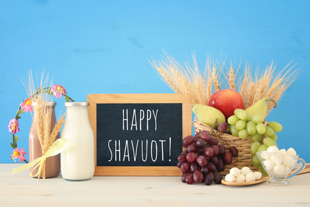 image of dairy products and fruits over wooden table. Symbols of jewish holiday - Shavuot