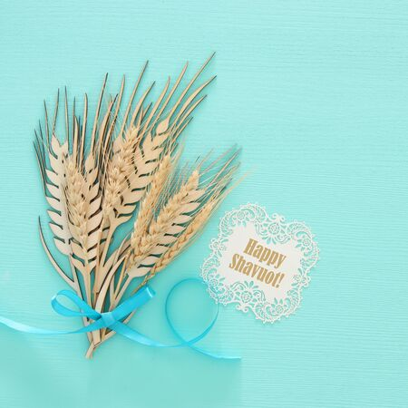top view of wooden wheat crop decoration over mint background. Symbols of jewish holiday - Shavuot Foto de archivo - 99902134