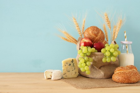 image of fruits, bread and cheese in the basket over wooden table