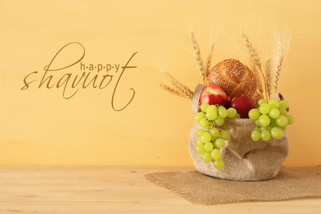 image of fruits and bread in the basket over wooden table