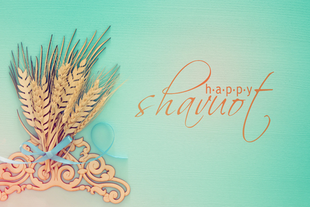 top view of wooden wheat crop decoration over mint background. Symbols of jewish holiday - Shavuot