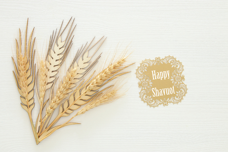 top view of wooden wheat crop decoration over white background. Symbols of jewish holiday - Shavuot Stock Photo