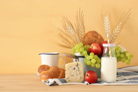 image of fruits, bread and cheese in the tin basket over wooden table