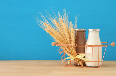image of milk and Chocolate in the basket with wheat over wooden table and pastel background. Symbols of jewish holiday - Shavuot. Stock Photo