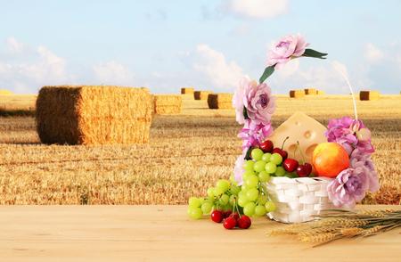 image de fruits et de fromage dans un panier décoratif avec des fleurs sur une table en bois. Symboles de la fête juive - Chavouot
