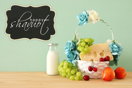 image of fruits and cheese in decorative basket with flowers over wooden table. Symbols of jewish holiday - Shavuot 版權商用圖片