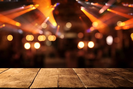 Image of wooden table in front of abstract blurred restaurant lights background Stock Photo