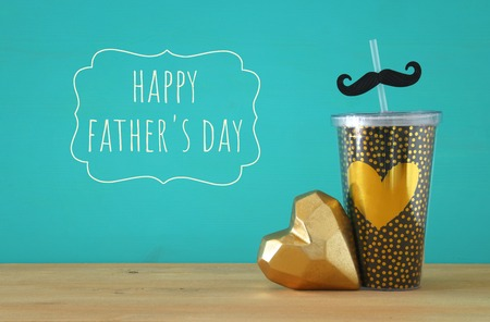 Image of black cup with golden heart. Father's day concept