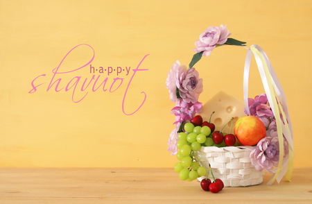 image of fruits and cheese in decorative basket with flowers over wooden table. Symbols of jewish holiday - Shavuot Фото со стока