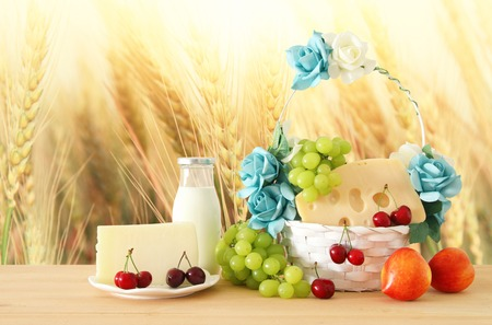 image of fruits and cheese in decorative basket with flowers over wooden table. Symbols of jewish holiday - Shavuot Stock Photo