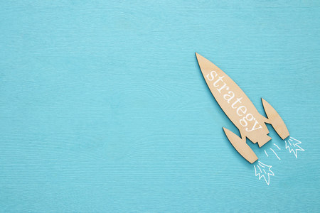 Top view of wooden rocket with word - strategy - over blue background