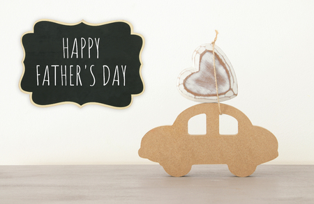 Image of wooden car with heart on the roof, present for dad. Father's day concept Фото со стока
