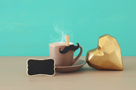 Image of cup of coffee and black mustache over wooden table. Fathers day concept Stock Photo