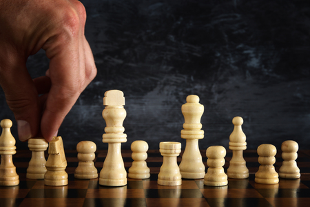 Image of businessman hand moving chess figure over chess board. Business, competition, strategy, leadership and success concept