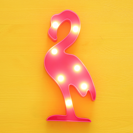 a plastic flamingo lamp with leds over yellow wooden background. holiday summer concept