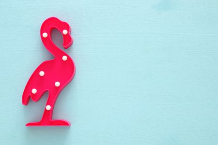 a plastic flamingo lamp with leds over blue wooden background. holiday summer concept