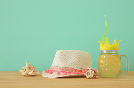 Image of fresh lemonade drink in cute pineapple shape glass with twisted straw next to beach fedora hat over wooden table Stock Photo