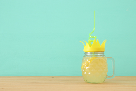 Image of fresh lemonade drink in cute pineapple shape glass with twisted straw over wooden table