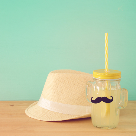 Image of fresh lemonade drink in cute cactus shape glasses wearing mustache, over wooden table. Fathers day concept Stock Photo