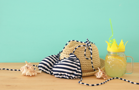 Image of fresh lemonade drink in cute pineapple shape glass with twisted straw next to bikini swimsuit and beach fedora hat over wooden table
