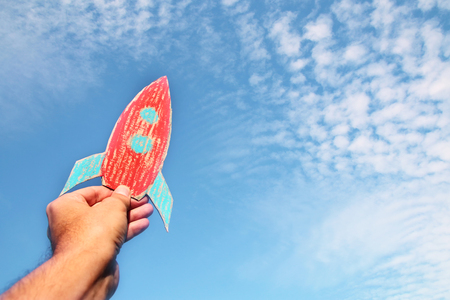 image of male hand holding a rocket against the sky. imagination and success concept Stock Photo