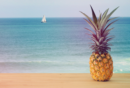 Pineapple on wooden table. Beach and tropical theme