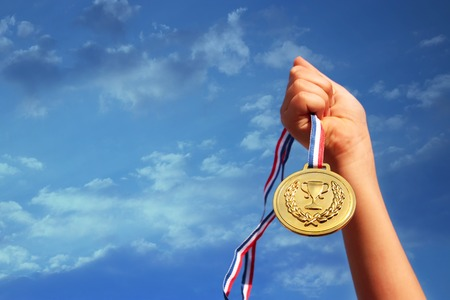 child hand raised, holding gold medal against sky. education, success, achievement, award and victory concept