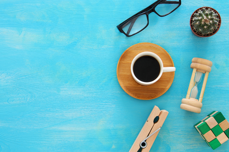 Mix of office supplies and gadgets on a blue wooden table background. top view