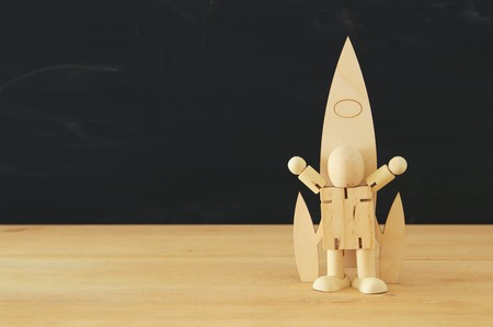 wooden rocket and dummy in front of classroom blackboard