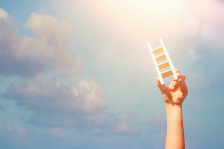image of child hand holding a ladder against the sky. education and success concept