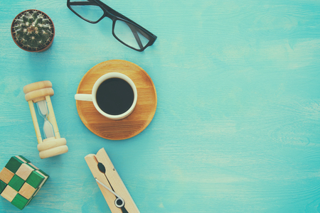 top view image of cup of coffee, glasses, hourglass on wooden table