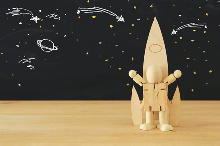 wooden rocket and dummy with space sketches in front of classroom blackboard