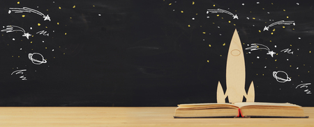 Back to school concept. wooden rocket and space sketchs over open book in front of classroom blackboard Stock Photo