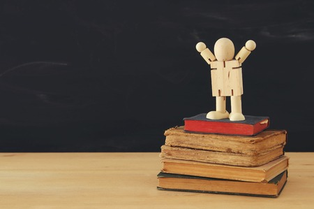 image of a wooden figure standing on a stack of books. Concept of success, education and back to school.