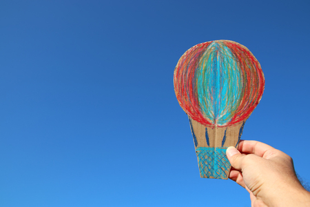 image of male hand holding hot air balloon against the sky. imagination and success concept Stock Photo
