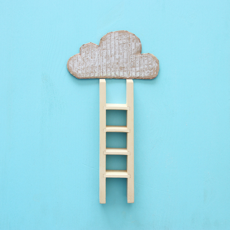 wooden ladder and cloud over wooden blue background. Stock Photo