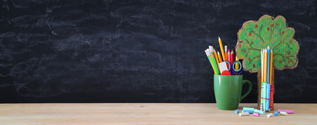 Back to school banner. tree of knowledge and pencils in front of classroom blackboard Stock Photo
