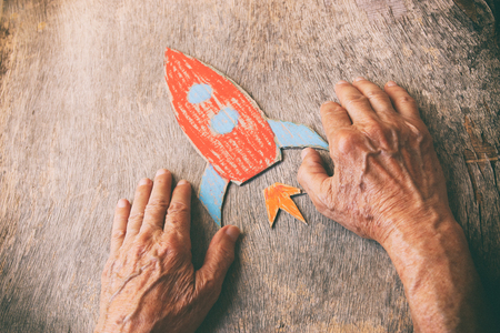 A close up of an elderly man holding a paper rocket on a wooden table. Concept of thinking about childhood dreams, sadness and loneliness. Stockfoto