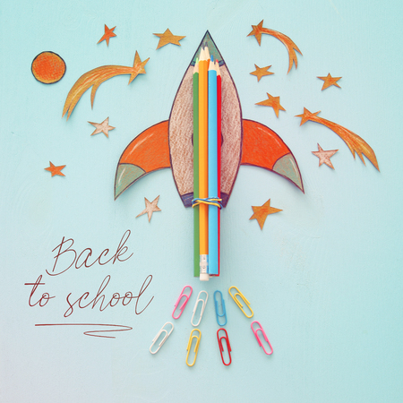 Back to school concept. rocket with pencils, space elements shapes cut from paper and painted over wooden blue background Stock Photo
