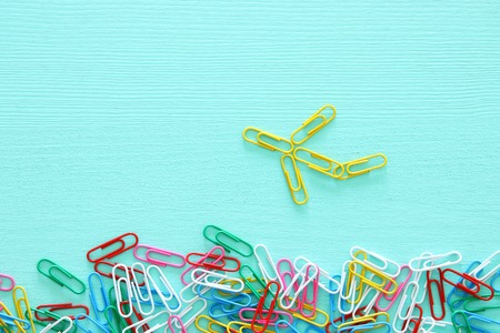 concept image of creativity or think outside the box. paperclips forming an airplane, teamwork and different mindset.