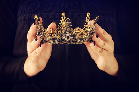 image of lady in black with holding queen crown decorated with precious stones. fantasy medieval period. Black queen Stock Photo