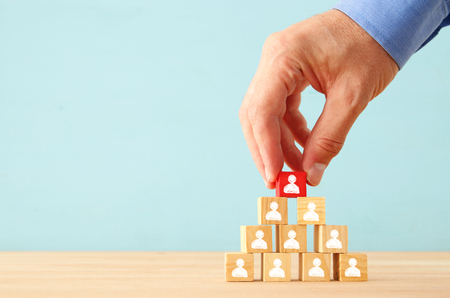image of wooden blocks with people icons over table ,building a strong team, human resources and management concept.
