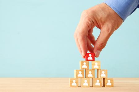 Bild von Holzklötzen mit Personenikonen über Tabelle, Aufbau eines starken Teams, Personal- und Managementkonzept.
