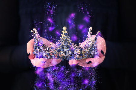 image of lady in black holding queen crown decorated with precious stones and magical glowing mysterious dust. fantasy medieval period. Black queen