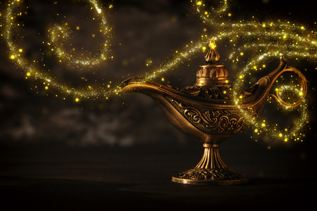 Image of magical mysterious aladdin lamp with glitter sparkle smoke over black background. Lamp of wishes Stock Photo